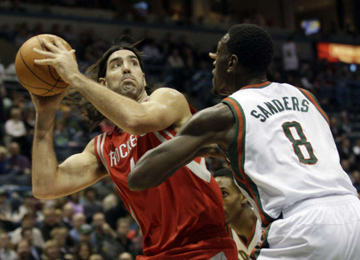 Rockets forward Luis Scola, left, looks to put up a shot over Bucks forward Larry Sanders during the first half.