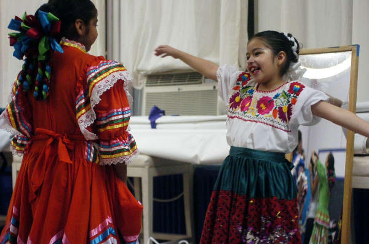 Rosa Rodríguez (der.) y Nicole Mata, ambas de 9 años, practican los movimientos durante una clase de danza folclórica en los salones de MECA.