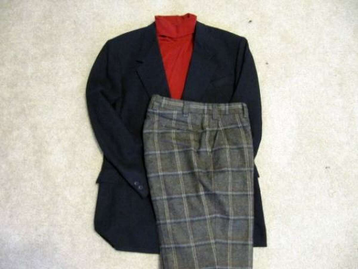 Light-colored plaid trousers contrast well with a blazer. The solid red turtleneck picks up the red stripe in the trousers.