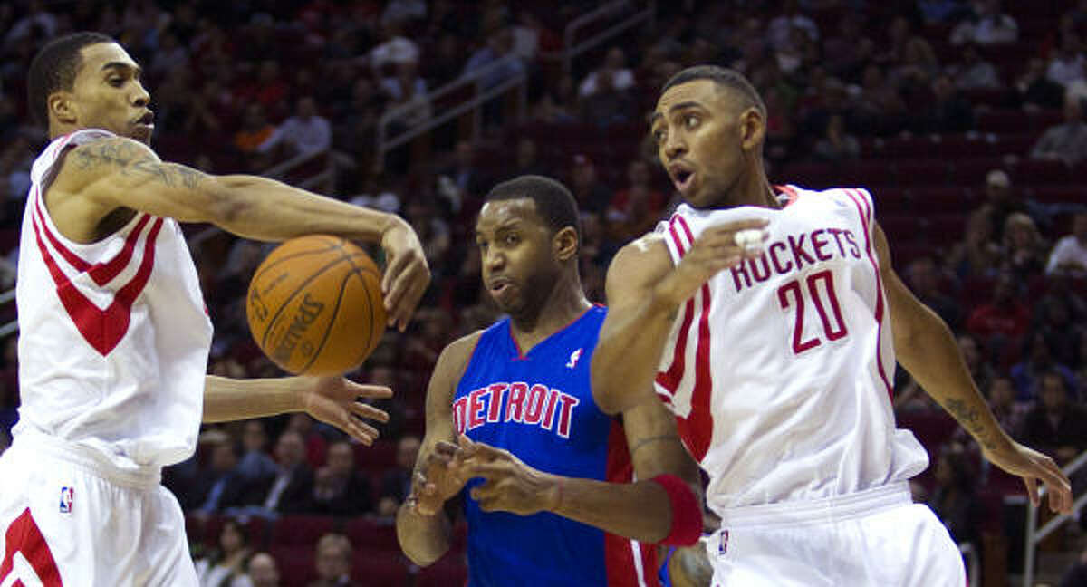 Rockets guard Courtney Lee, left, grabs a rebound away from Pistons guard Tracy McGrady as Rockets power forward Jared Jeffries looks back during Tuesday night's victory.