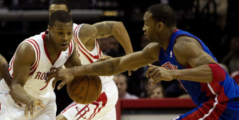 Rockets point guard Kyle Lowry has the ball knocked out of his hands by Pistons guard Tracy McGrady during the first half. Photo: Brett Coomer, Chronicle