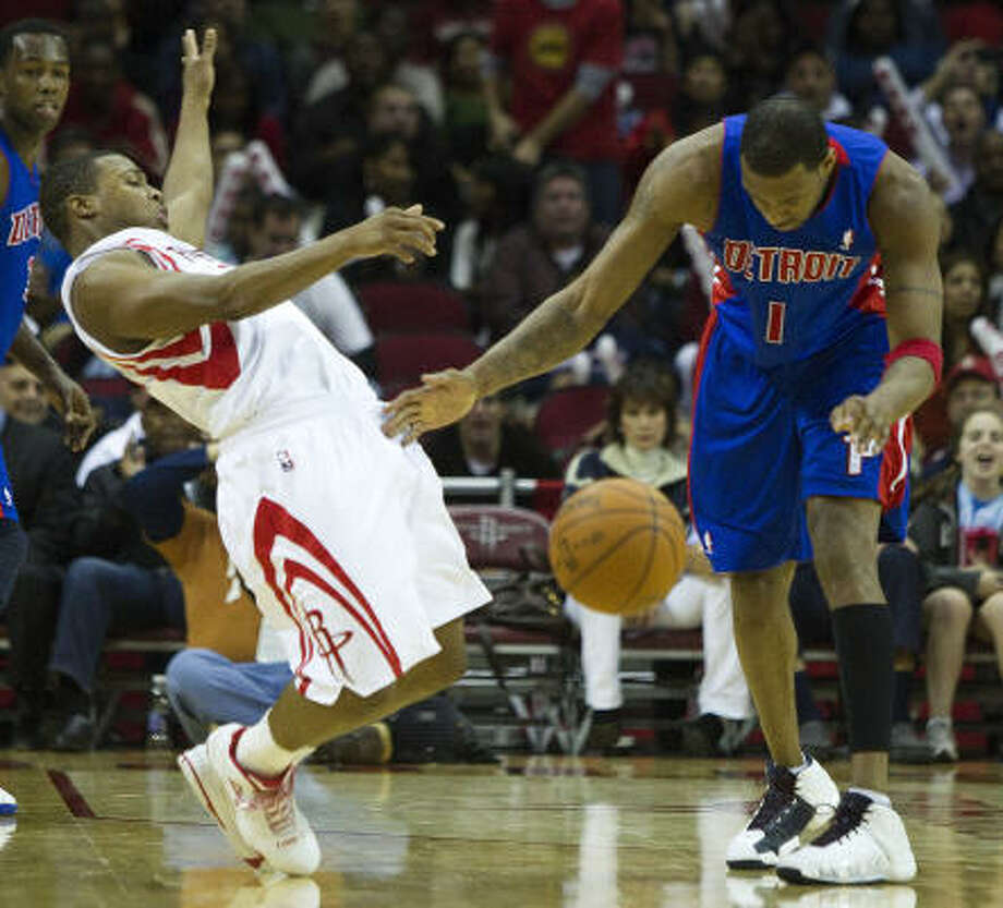 Rockets point guard Kyle Lowry, left, recoils after being fouled by Pistons guard Tracy McGrady (1) during the second half. Photo: Brett Coomer, Chronicle