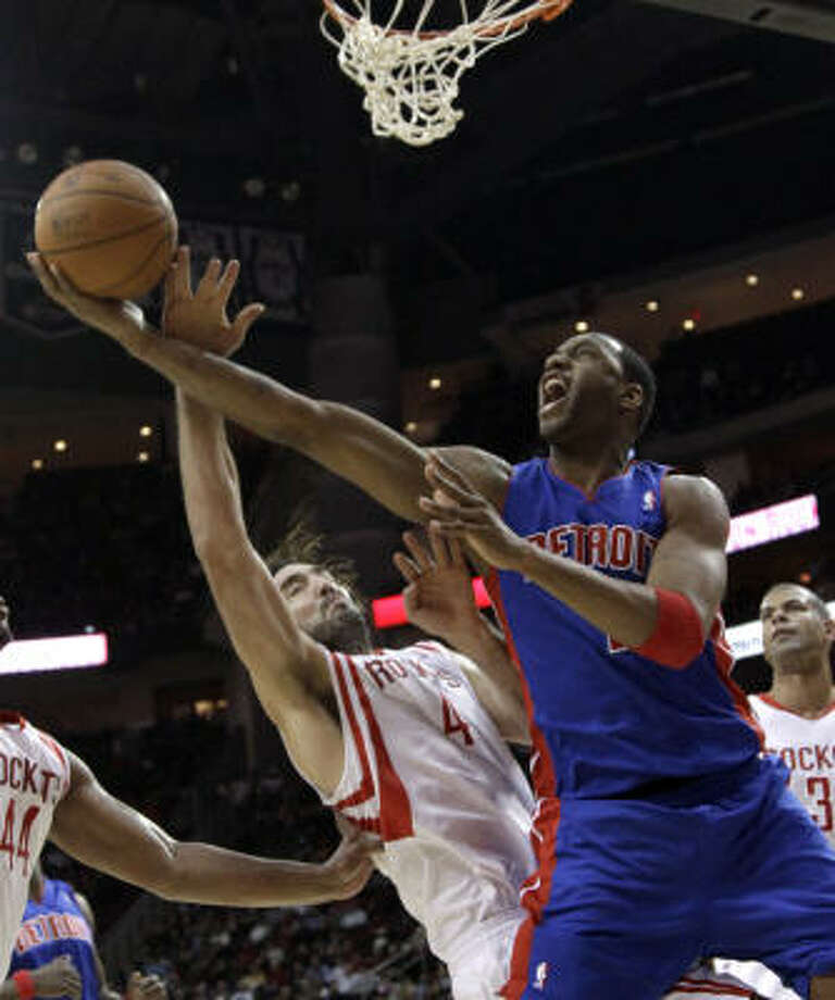 Pistons guard Tracy McGrady, right, is fouled by Rockets forward Luis Scola during the first quarter. Photo: David J. Phillip, AP