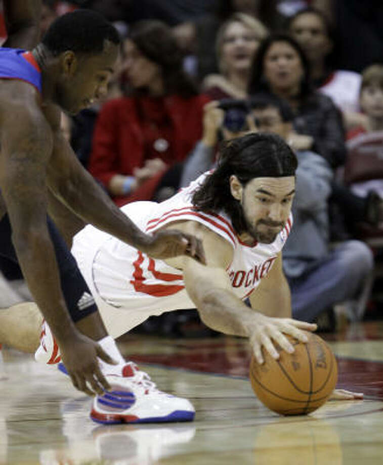 Rockets forward Luis Scola, right, dives for a loose ball with Pistons guard Rodney Stuckey, left, during the first quarter. Photo: David J. Phillip, AP