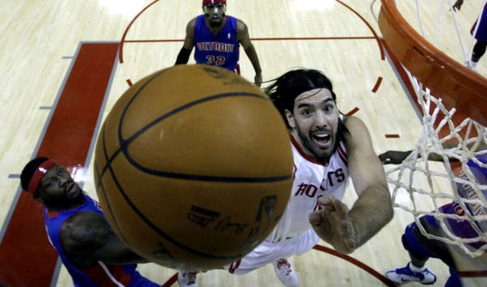 Rockets forward Luis Scola, right, goes up for a shot as Pistons center Ben Wallace, left, defends d