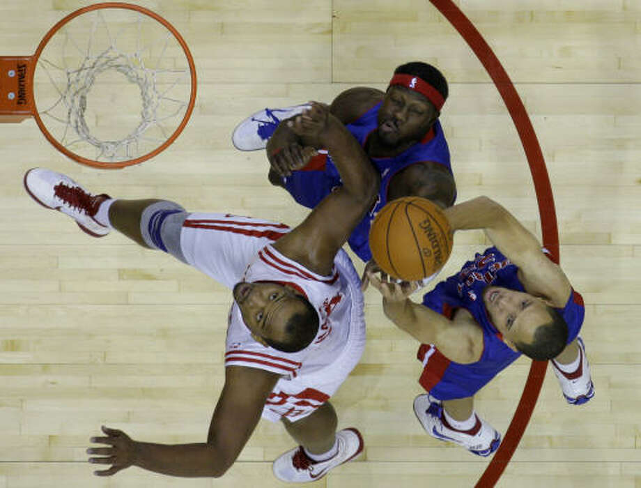 Rockets center Chuck Hayes, left, and Pistons forward Tayshaun Prince, right, and Ben Wallace, center, go up for a rebound during the first quarter. Photo: David J. Phillip, AP