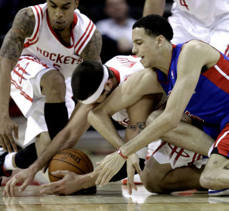 Pistons small forward Austin Daye, right, battles with Rockets center Brad Miller for a loose ball as Courtney Lee, left, reaches in during the fourth quarter. Photo: David J. Phillip, AP