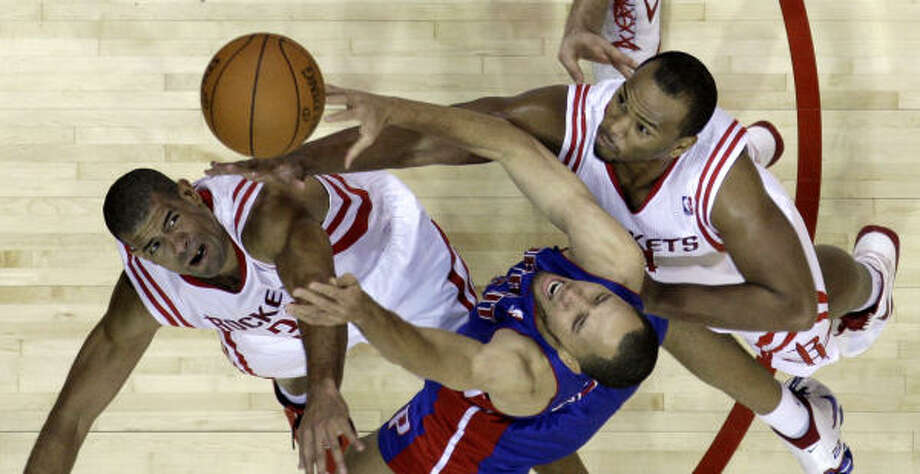 Pistons forward Tayshaun Prince, center, goes up for a rebound with Rockets forward Shane Battier, left, and center Chuck Hayes, right, during the third quarter. Photo: David J. Phillip, AP