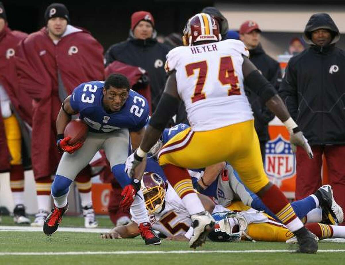 Giants 31, Redskins 7 Giants cornerback Corey Webster picks up one of three fumbles by Redskins quarterback Donovan McNabb.