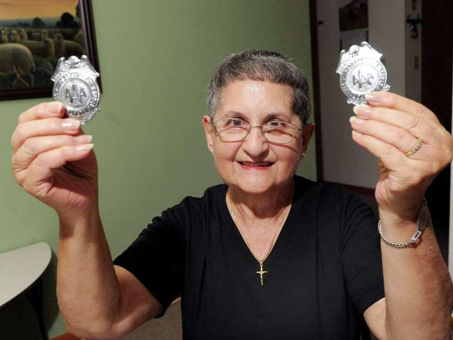 Rose Marie Balog holds up the two safety patrol badges that were issued to her by the Greenwich Police Department when she was a school crossing guard at Cos Cob School from 1949 through 1952. Balog, shown here in  in her Riverside home, Wednesday afternoon, Aug. 3, 2011, said she wants to return the badges to the police. Photo: Bob Luckey / Greenwich Time