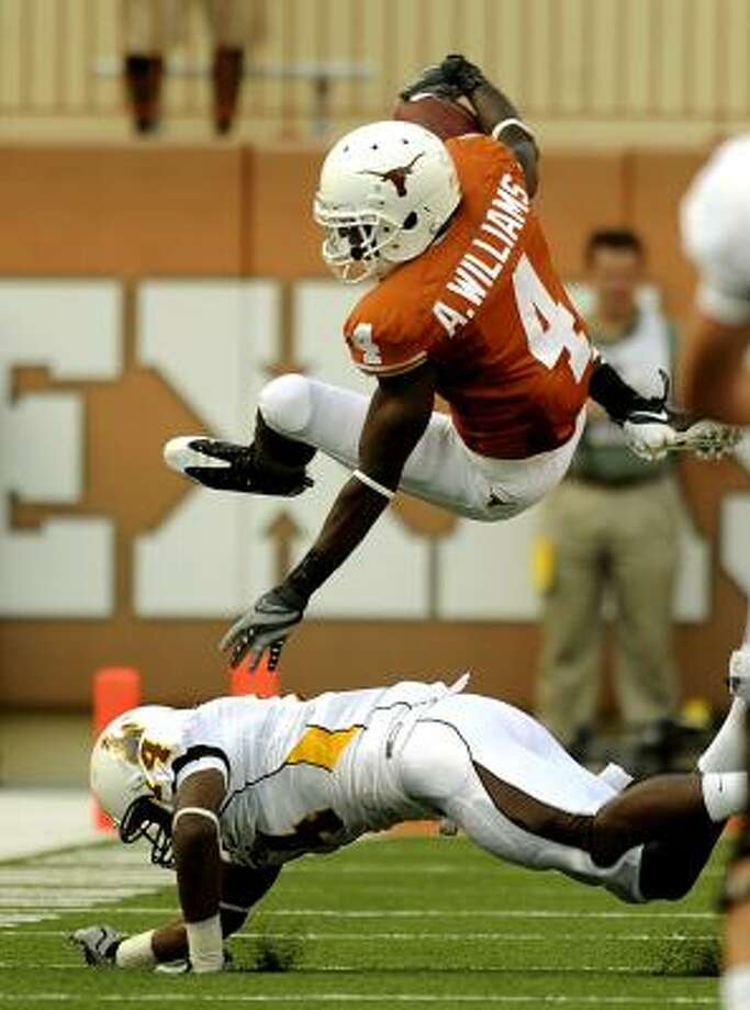 Texas' Darius White is upended by Wyoming's Marqueston after a long punt return in the first half. Photo: BILLY CALZADA, SAN ANTONIO EXPRESS-NEWS