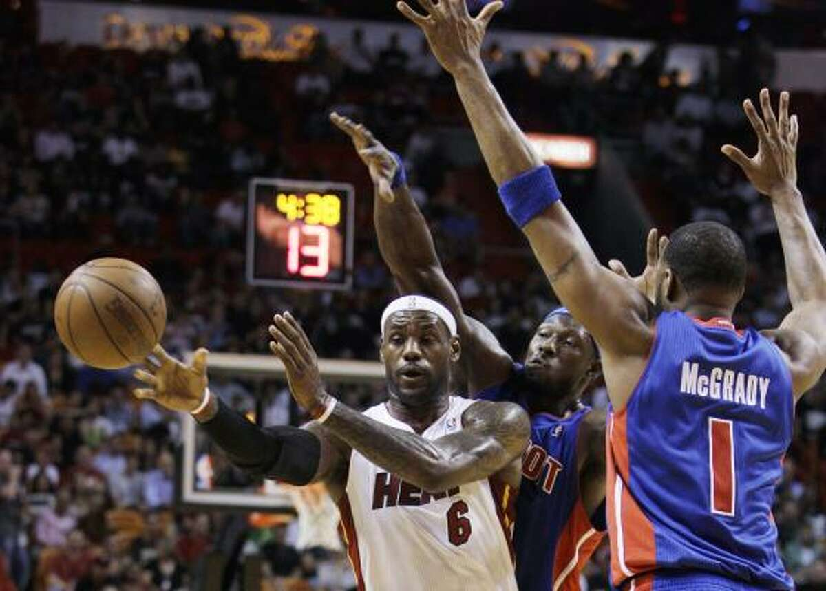 Heat forward LeBron James looks to pass against Detroit Pistons center Ben Wallace, rear, and guard Tracy McGrady during the first quarter. James scored 12 points in the first quarter.