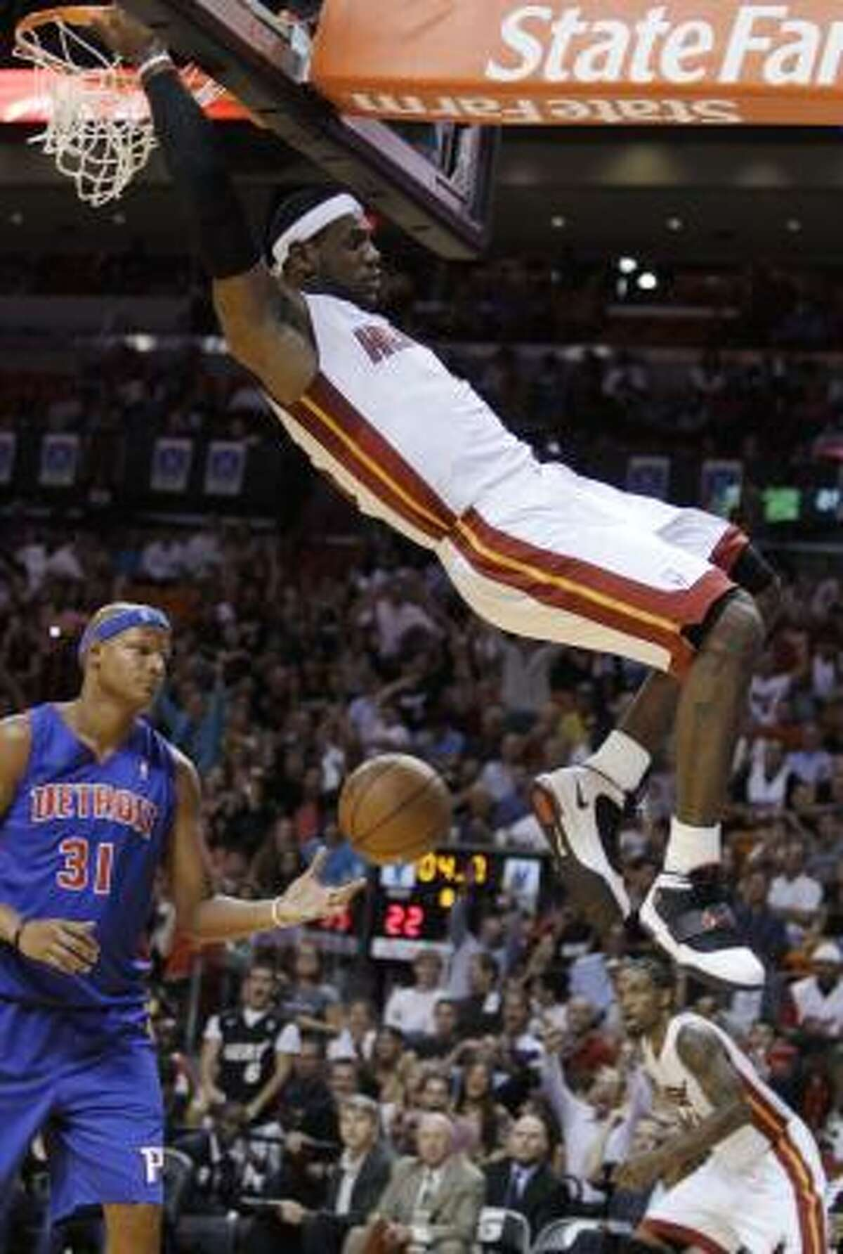 LeBron James, right, dunks as Pistons forward Charlie Villanueva (31) looks on during the first quarter.