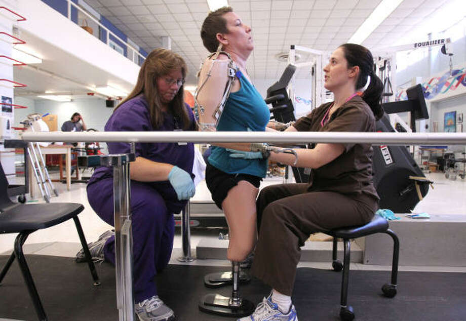 Hayes gets some help from Jamie Lottinger and Heather Zissman at The Institute for Rehabilitation and Research.  Hayes endured weeks of intense physical therapy. Photo: Billy Smith II, Chronicle