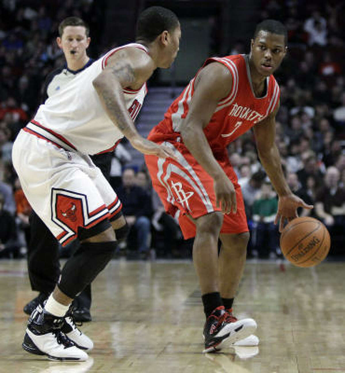 Rockets guard Kyle Lowry, right, looks to a pass against Bulls guard Derrick Rose during the first quarter on Saturday.