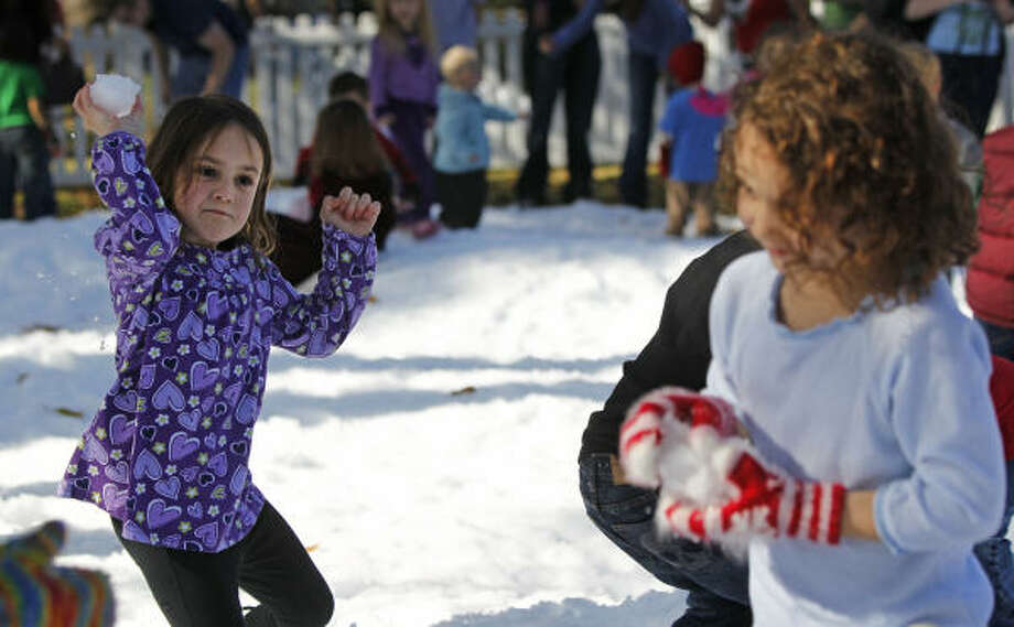 Maddie Weller, left, 5, of Houston throws a snowball at her sister, Sadie Weller, 4, right, during the Annual Snow Flurry at the Houston Museum of Natural Science in Houston.  The winter wonderland was made of 80,000 pounds of snow and events included arts and crafts and Santa with a live reindeer. Photo: Melissa Phillip, Houston Chronicle