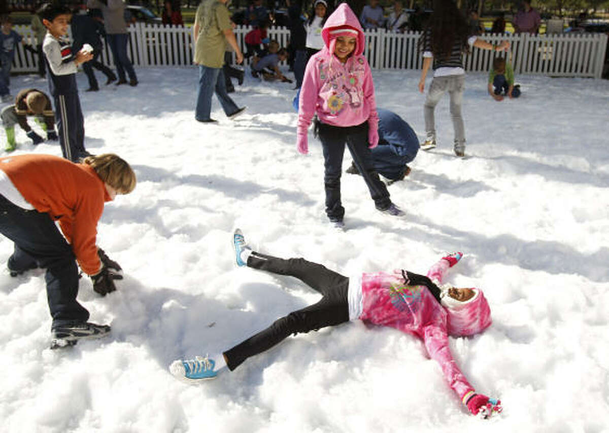 Victoria Jackson, 7, bottom right, of Houston makes a snow angel as her friend, Adana Ards, 7, top right, of Houston plays during the Annual Snow Flurry at the Houston Museum of Natural Science.