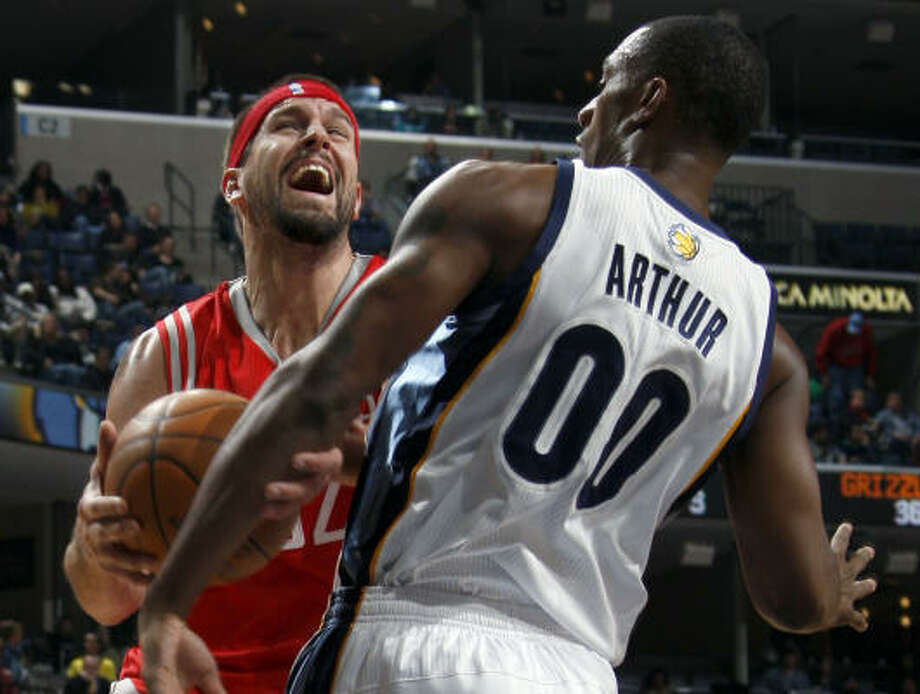 Rockets center Brad Miller, left, reacts as he is fouled by Grizzlies forward Darrell Arthur in the first half. Photo: Nikki Boertman, AP