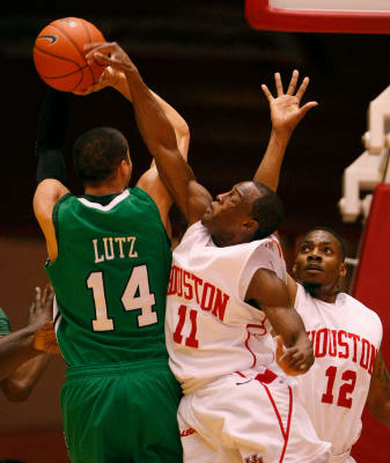 Marshall guard Chris Lutz (14) has his shot blocked by the shortest player on the court, UH guard Desmond Wade, in the first half of Saturday's game. Photo: Nick De La Torre, Chronicle
