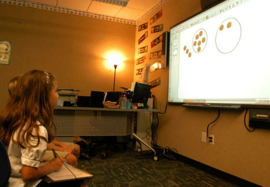 'SMART' LEARNING: Third-grade pupil Caroline Noyola works on her school work with the use of a smart board at the Grace School. The smart board is one of several improvements made to its third-grade classrooms. Photo: George Wong, For The Chronicle