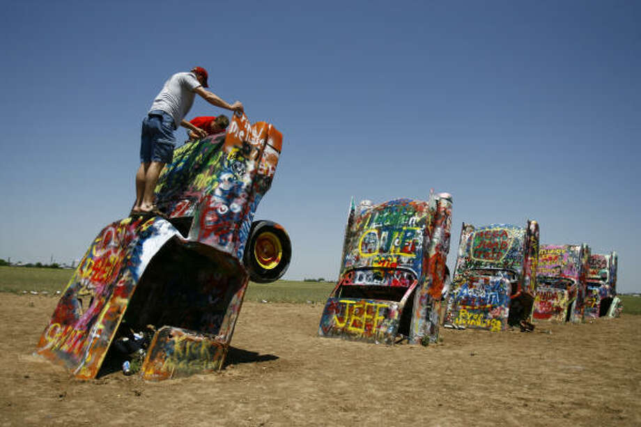 Rick Quattlebaum, helps his son Kyzer, 7, write his name on one of the Cadillacs at the Cadillac Ranch in Amarillo. Photo: Nick De La Torre, Houston Chronicle