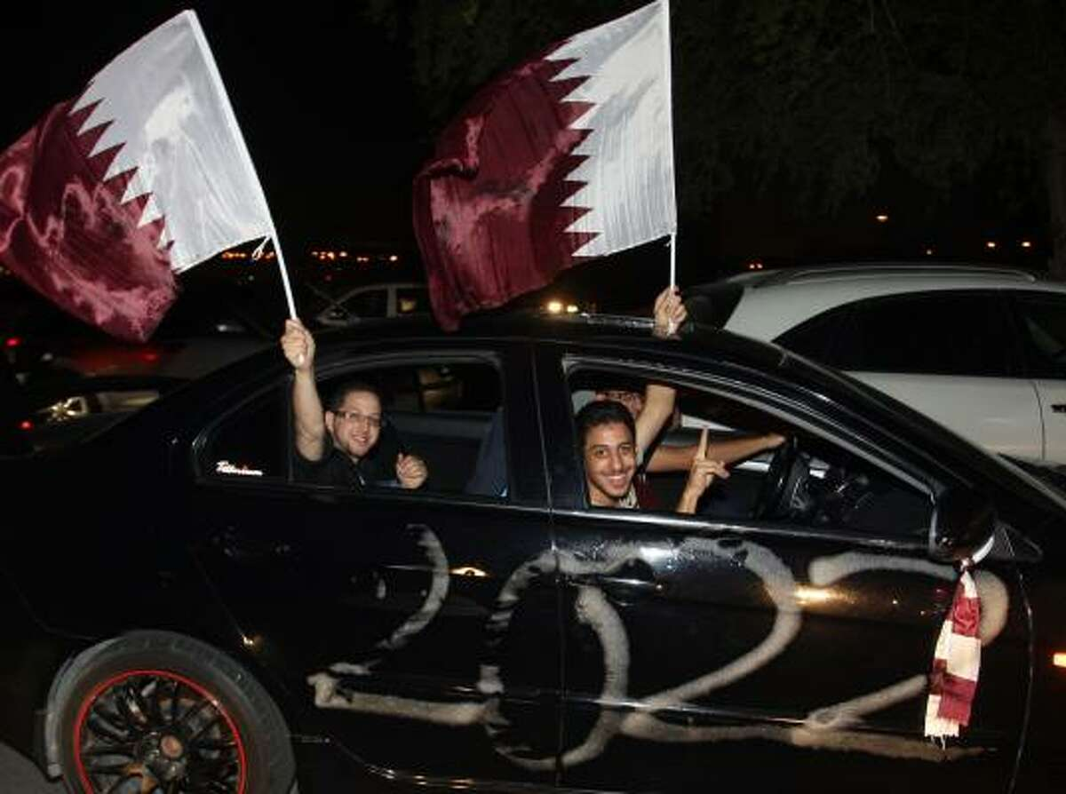 Qataris in Doha celebrate in the streets their successful bid to host the 2022 World Cup.