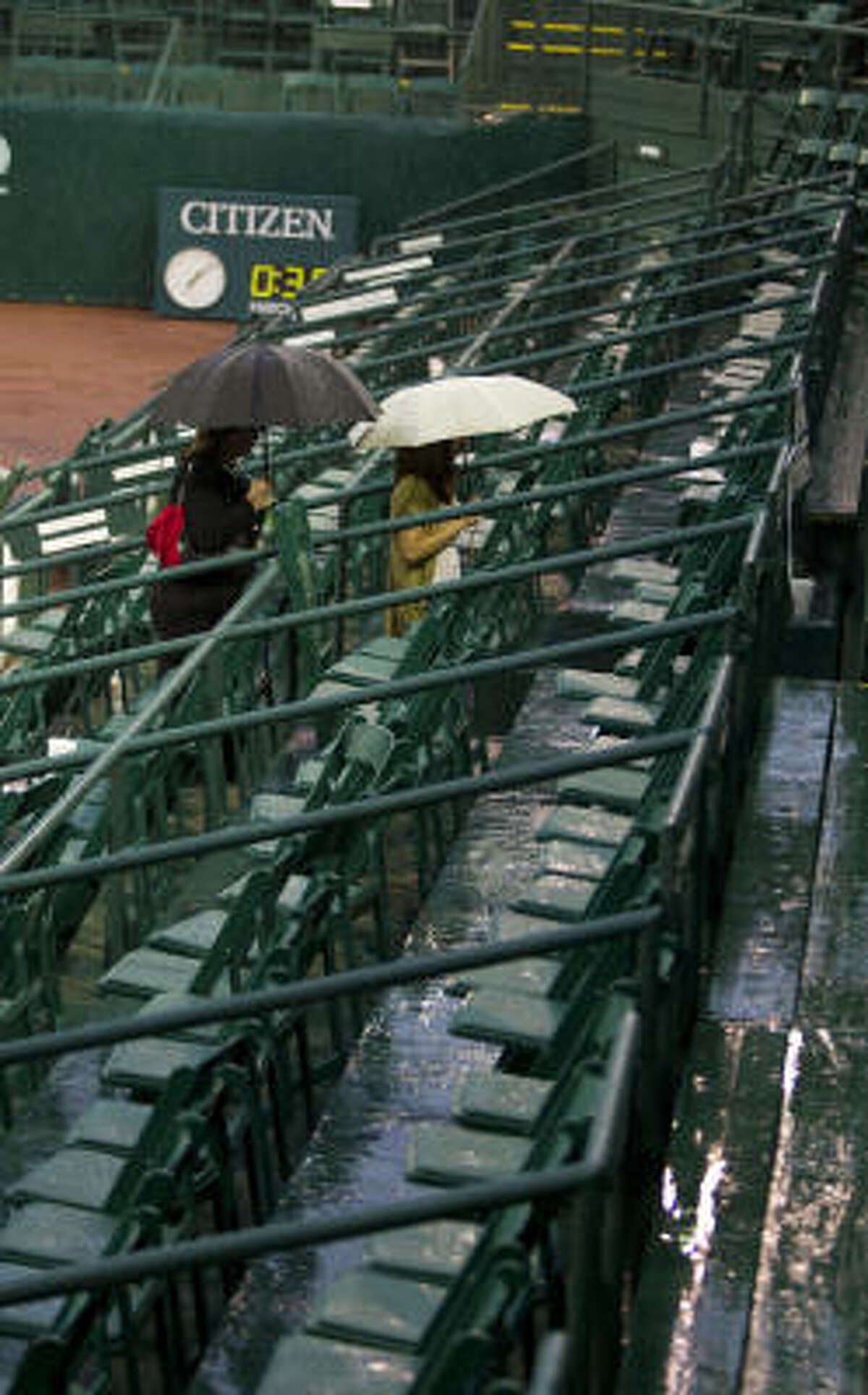 Tennis fans take cover under umbrellas during a rain delay at the U.S. Clay Court Championships on Wednesday, April 7, 2010.