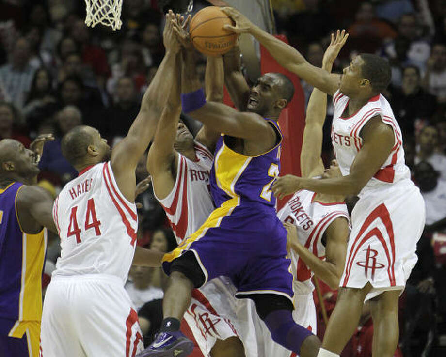 Dec. 1: Rockets 109, Lakers 99 Lakers guard Kobe Bryant gets stopped by a host of Rockets while on his way to the basket during the first half. Photo: Karen Warren, Chronicle