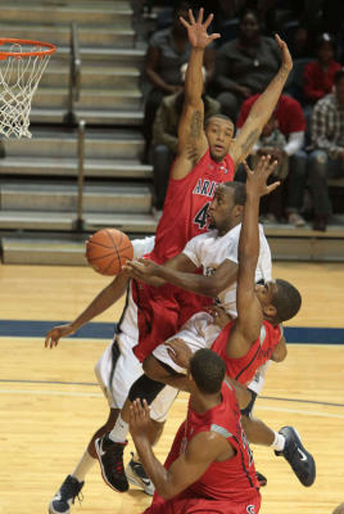 Rice guard Tamir Jackson, center, goes to the hoop while a host of Arizona players tries to stop him.