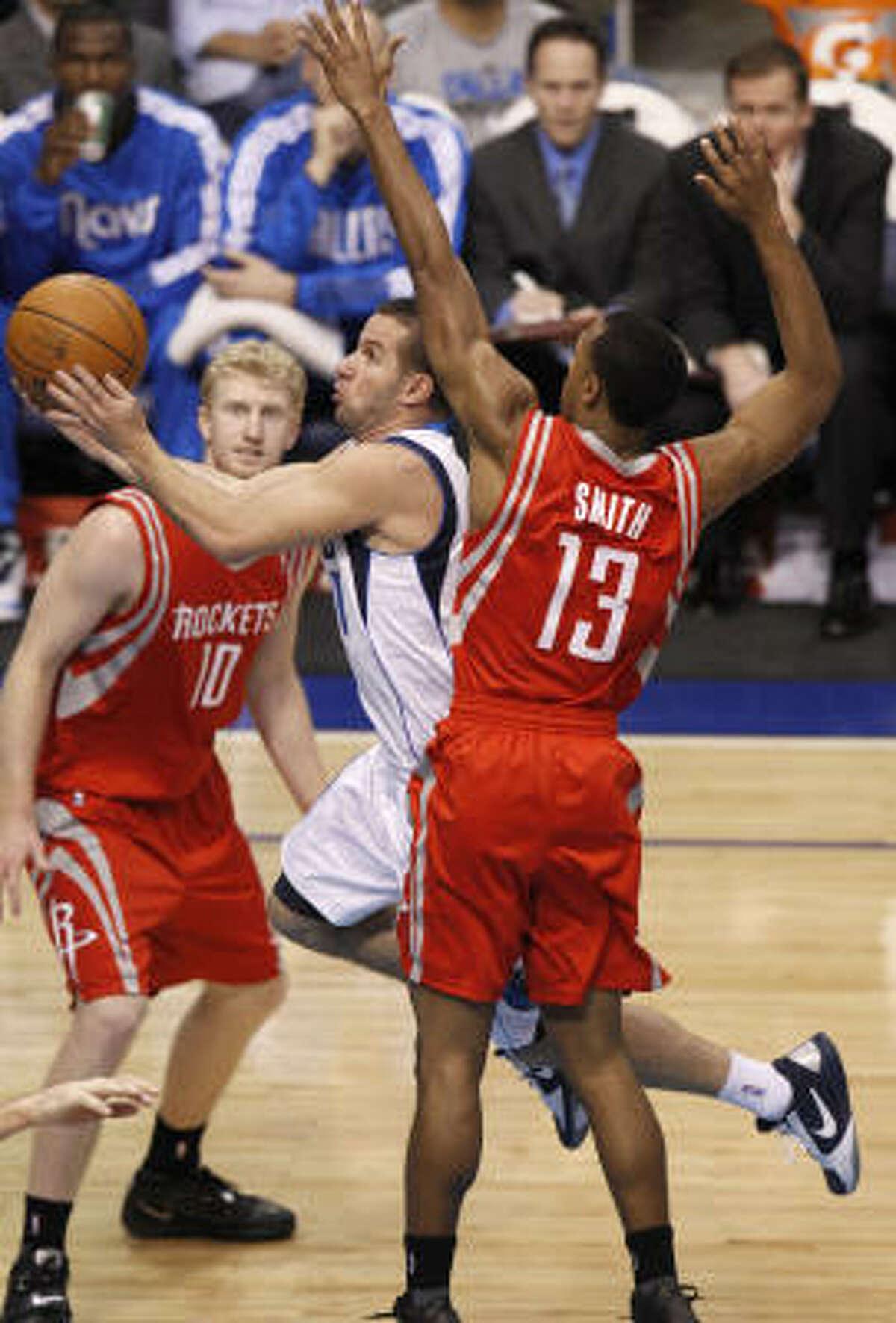 Mavericks point guard Jose Juan Barea, center, drives between Rockets point guard Ishmael Smith (13) and Chase Budinger (10).