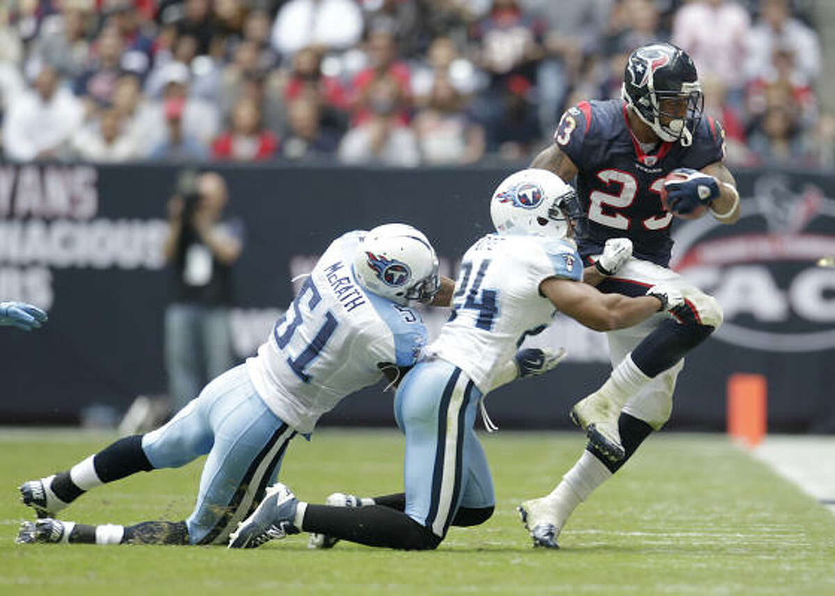 Texans running back Arian Foster (23) runs up the field before being tackled by Titans safety Chris Hope (24) and linebacker Gerald McRath (51) during the second quarter.