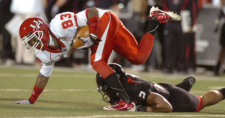 Nov. 27: Texas Tech 35, UH 20UH wide receiver Patrick Edwards tries to keep his balance after being hit by Texas Tech's Cornelius Douglas. Photo: Zach Long, AP