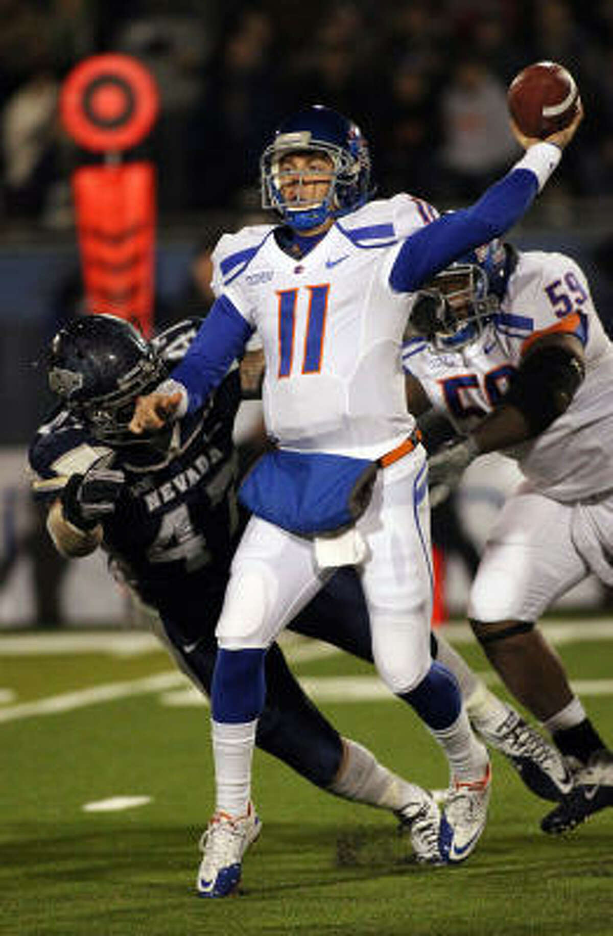 Boise State quarterback Kellen Moore delivers a passe under pressure in the first quarter.