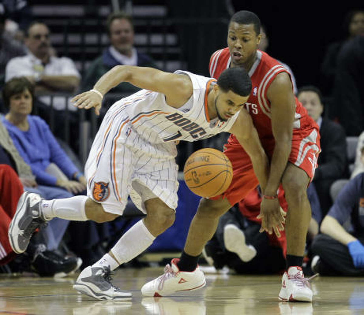 Bobcats guard D.J. Augustin, left, and Rockets guard Kyle Lowry, right, chase a loose ball.