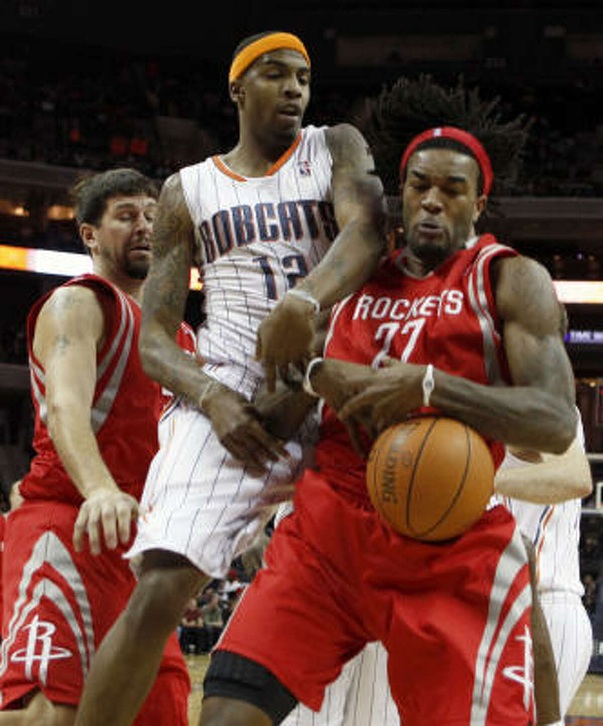 Rockets forward Jordan Hill (27) and Bobcats forward Tyrus Thomas (12) fight for control of a rebound as Rockets center Brad Miller, back left, tries to assist.