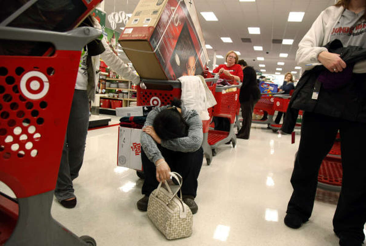 Black Friday bargain hunter Trinh Pham of Arlington takes a break in line at a Target store in Allen after waiting since 9 p.m. Thursday night to get in.