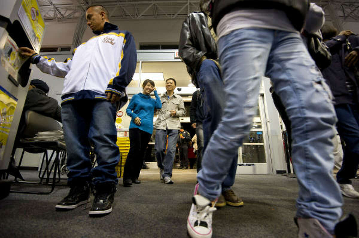 Early morning shoppers scurry through the door at Best Buy, which opened at 5 a.m. in Atlanta Friday.