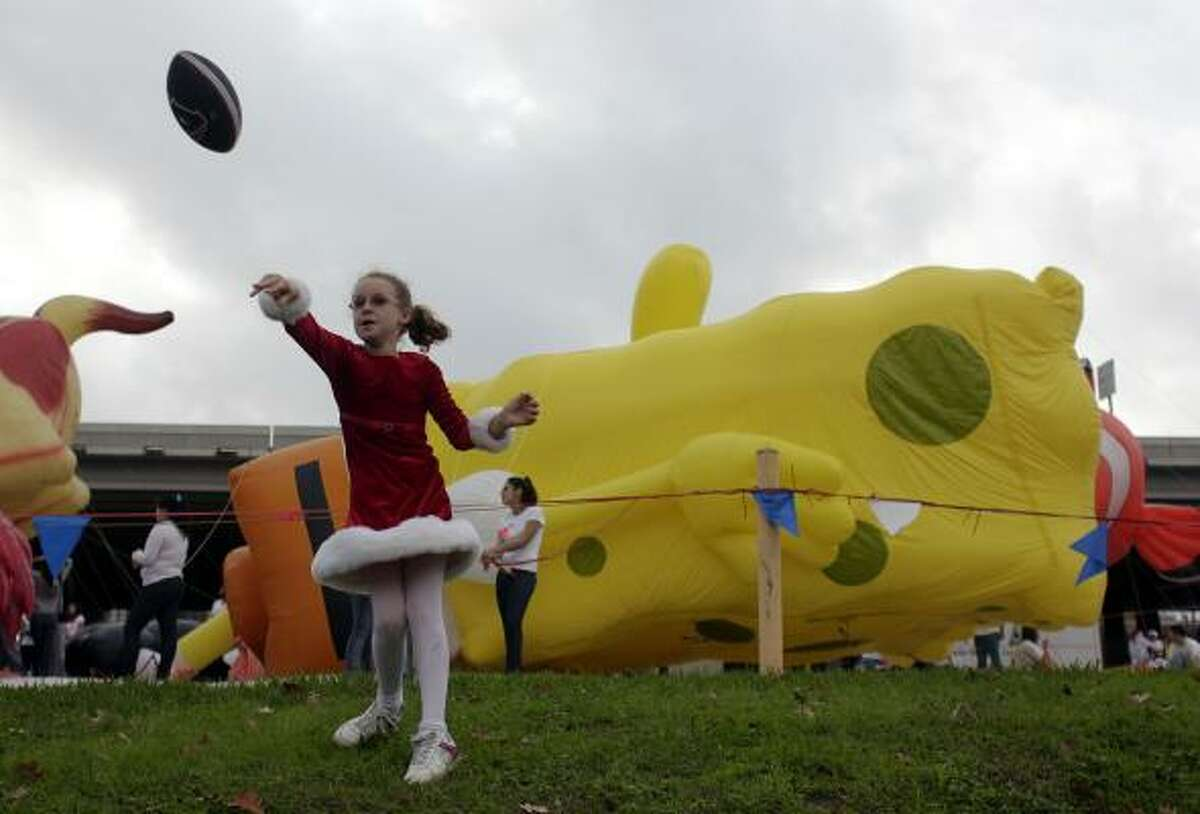 Kayli Eribarne, 10, throws a football next to an inflatable SpongeBob SquarePants.