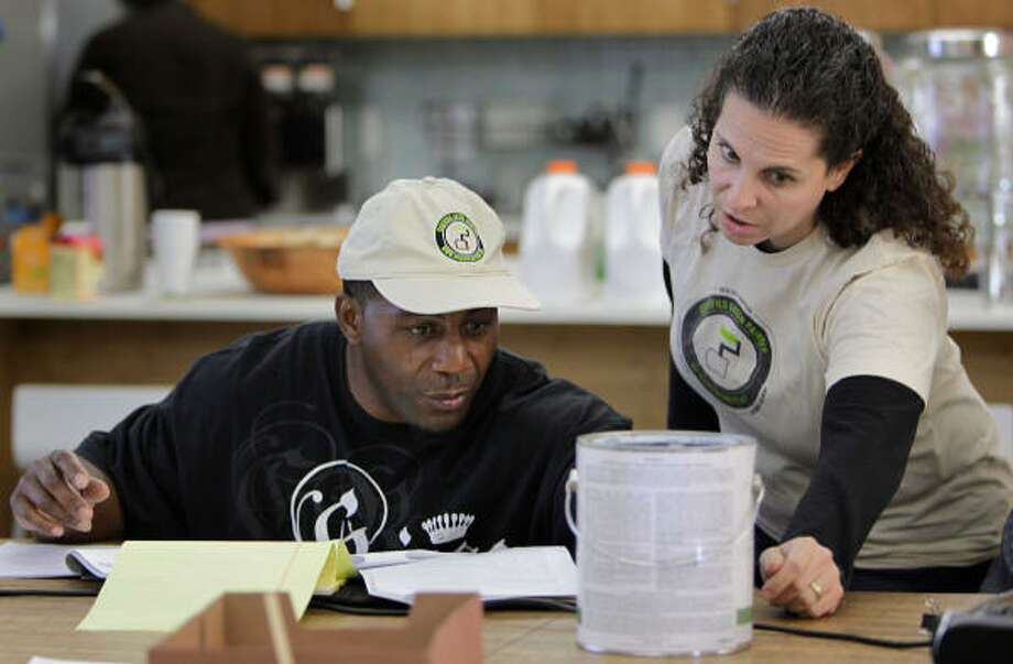 John Smith, an independent contractor, and Jennifer Touchet, a partner with Rice Village building materials store New Living and instructor, discuss chemicals in paint during a green painter certification class at the store. Photo: Mayra Beltran :, Chronicle