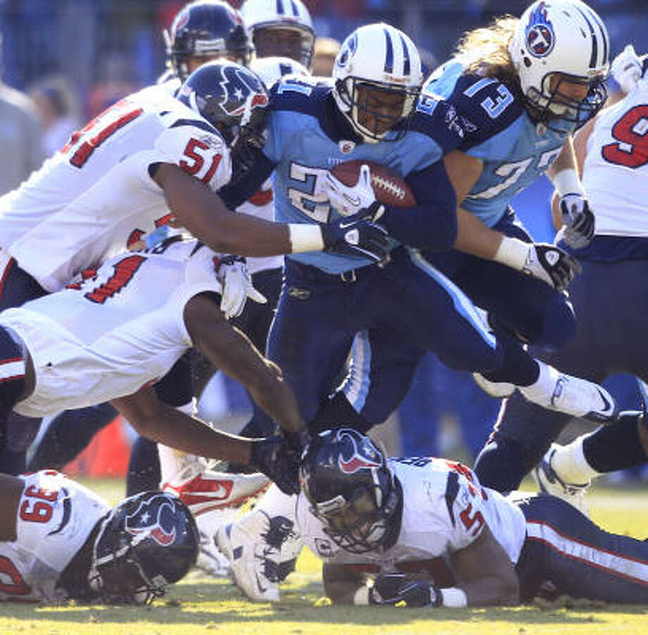 Despite five white jerseys in the vicinity, Titans running back Javon Ringer (21) is able to bull his way through the Texans' defense in the second quarter on Sunday. Photo: Brett Coomer, Chronicle