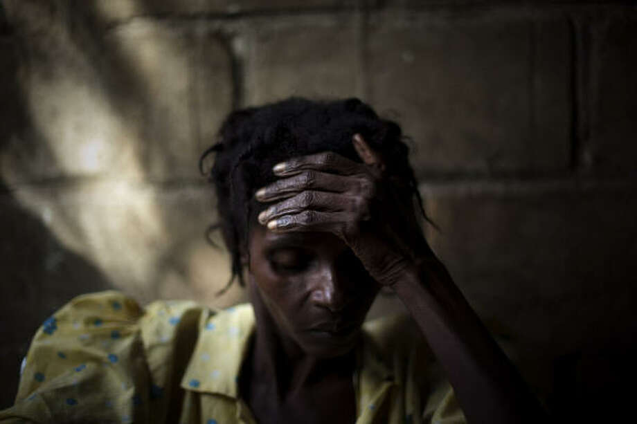 A woman with cholera symptoms waits for treatment at a public hospital in Limbe village near Cap Haitian, Haiti. Thousands of people have been hospitalized for cholera across and at least 1,100 people have died. Photo: Emilio Morenatti, AP