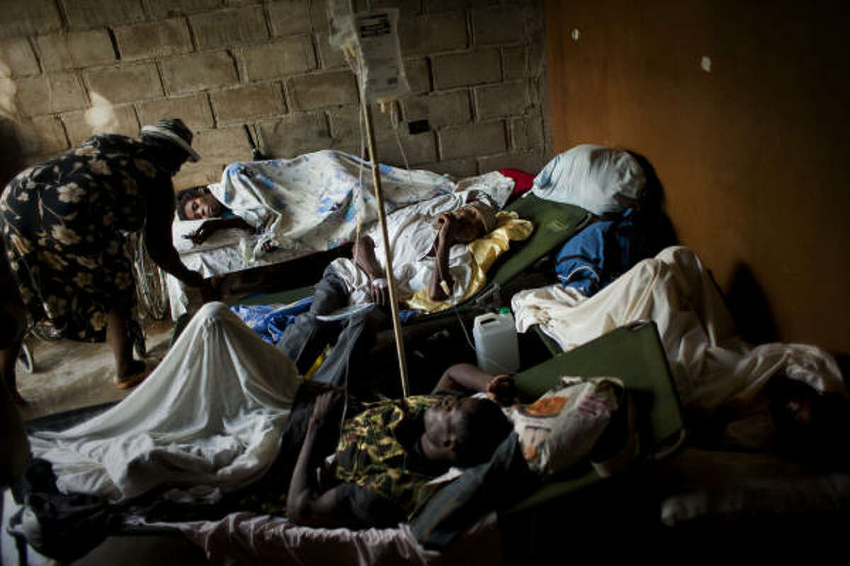 People suffering cholera symptoms rest on stretchers as they crowd the entrance of a public hospital in Limbe village near Cap Haitian, Haiti.
