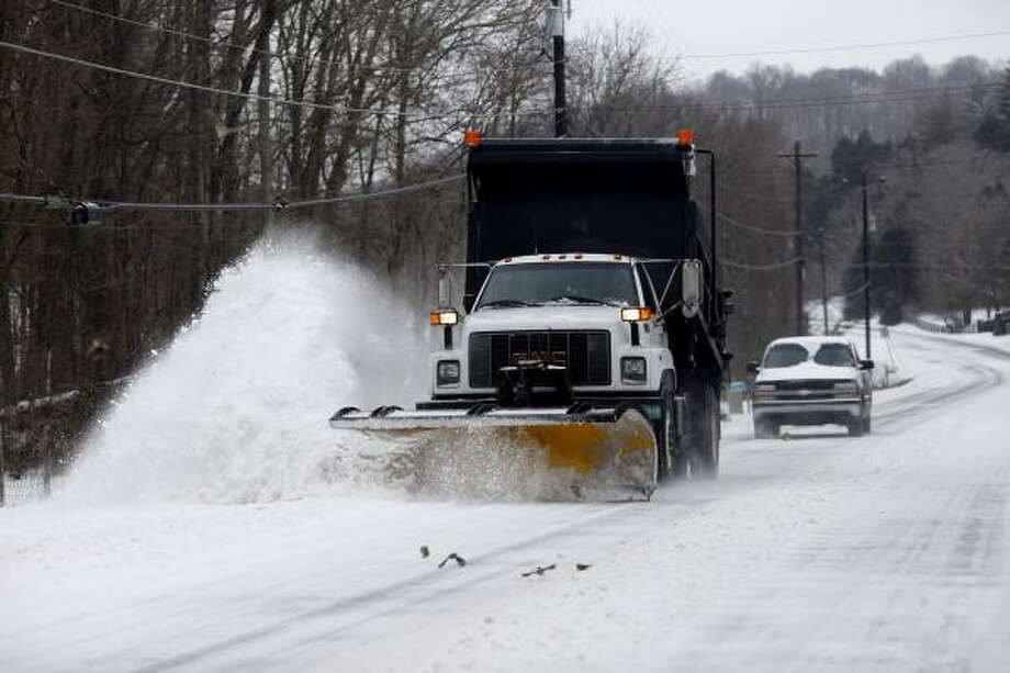 A snow plow clears the road in Peagram, Tenn., on Saturday. Photo: Josh Anderson, Associated Press