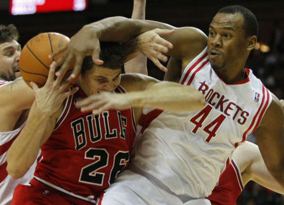 Bulls guard/forward Kyle Korver, left, and Rockets Chuck Hayes forward, right, tangle for a rebound during the fourth quarter. Photo: Melissa Phillip, Chronicle