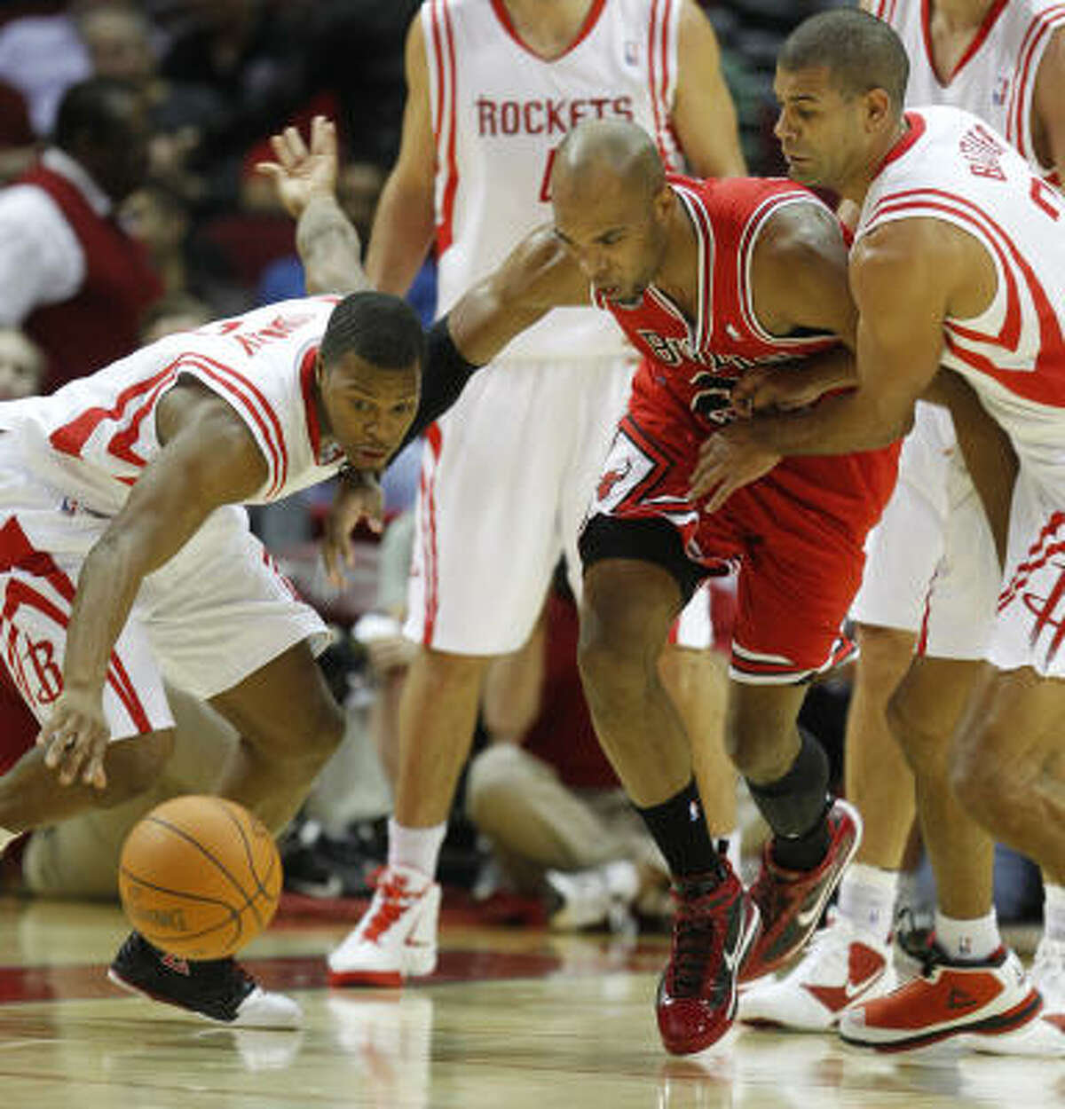 Rockets guard Kyle Lowry, left, and forward Shane Battier, right, battle Bulls forward Taj Gibson, center, for a loose ball during the first quarter.
