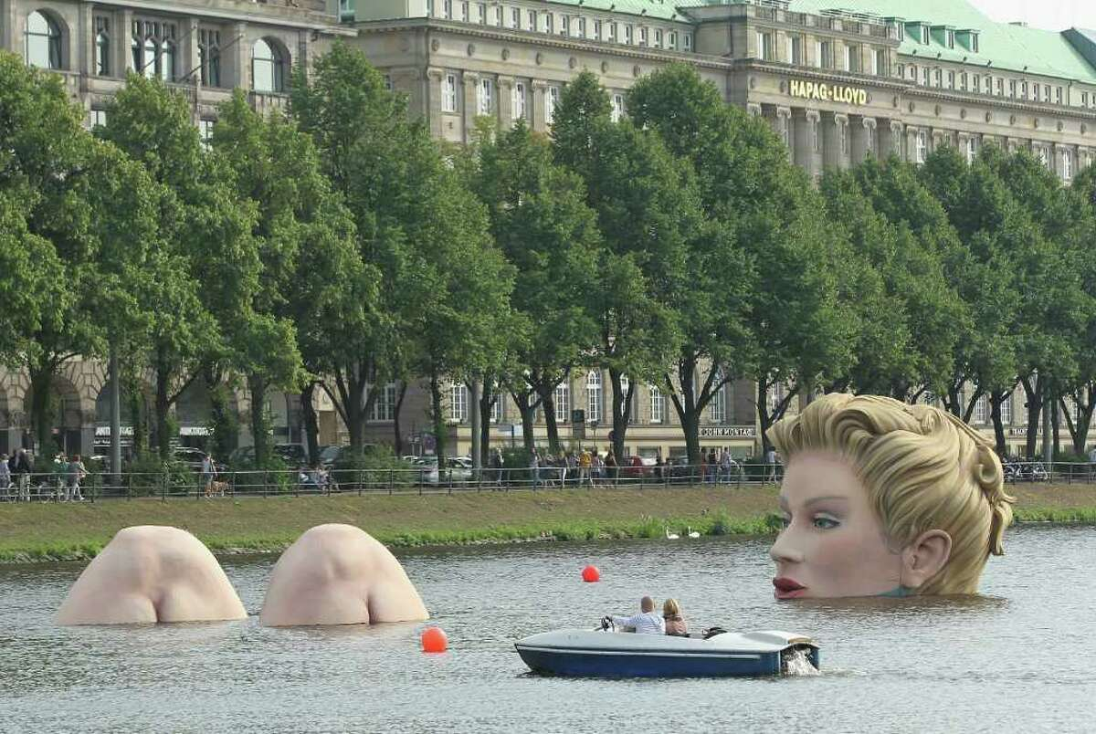 """Two people in a boat approach """"Die Badende"""" on August 3, 2011 in Hamburg, Germany."""