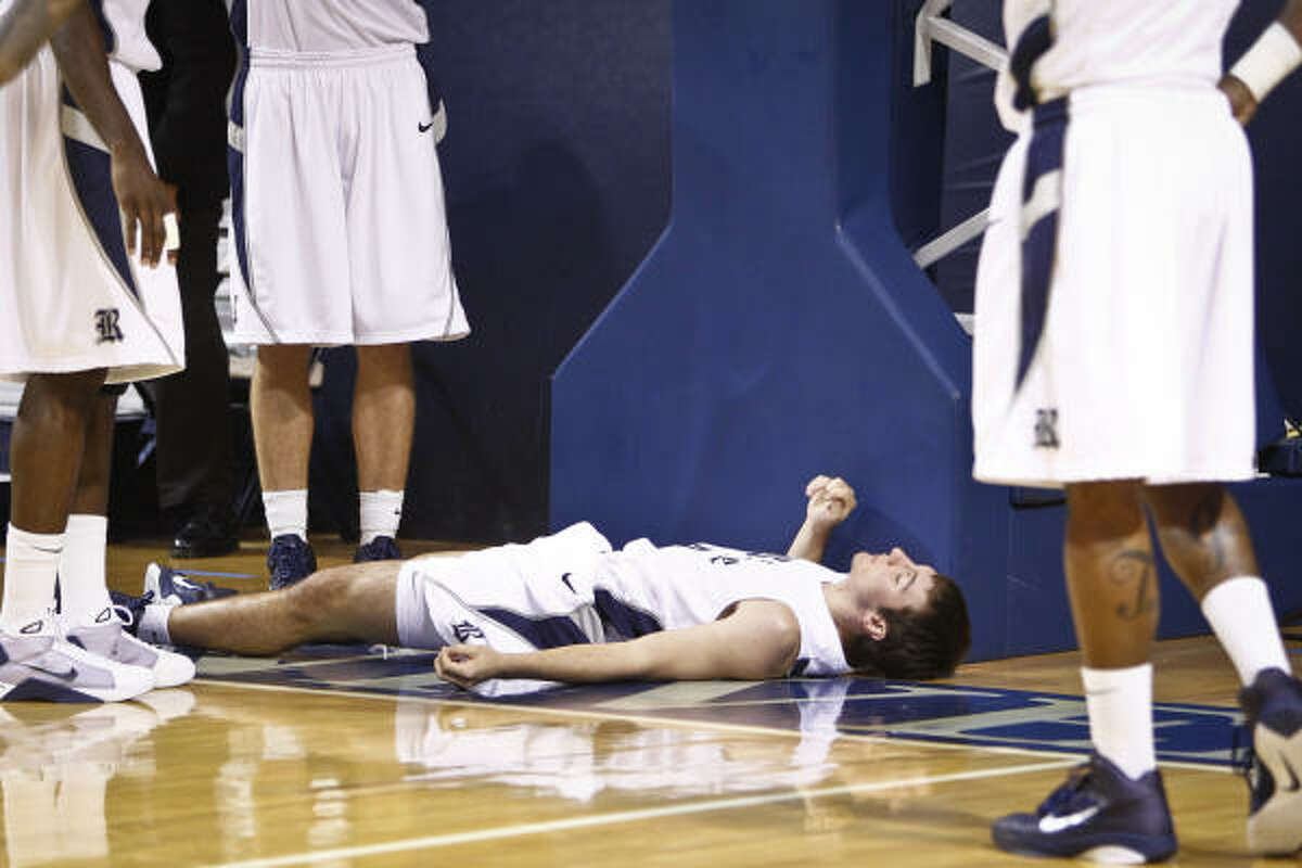 Rice's Connor Frizzelle (4) rests on the ground after a hard foul that forced him to leave the game.