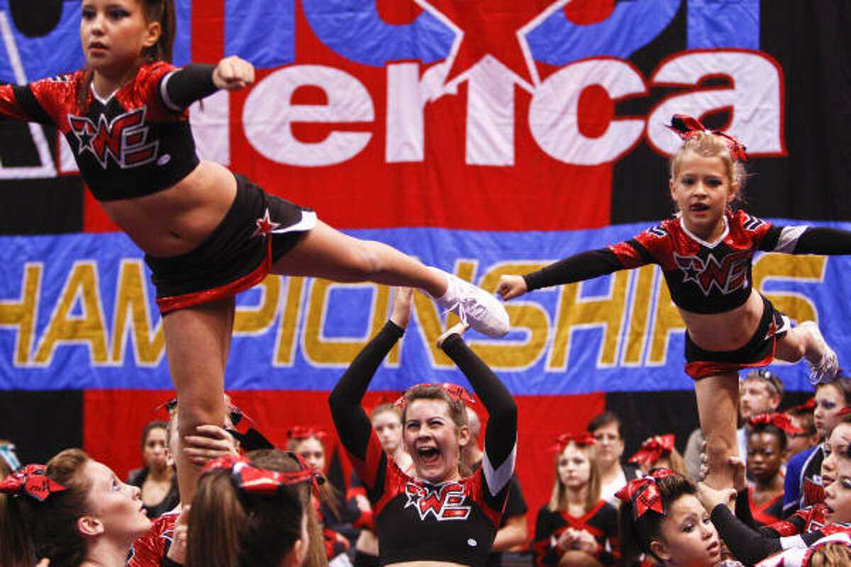 Courtney Poenticzh, 13, (middle) cheers on her teammates, Tatiana Rivas, 9, (left) and Haley McWhirter (right) members of the Woodlands Elite Airborne, during the Cheer America Platinum Championship dance competition at Reliant Arena in Houston.