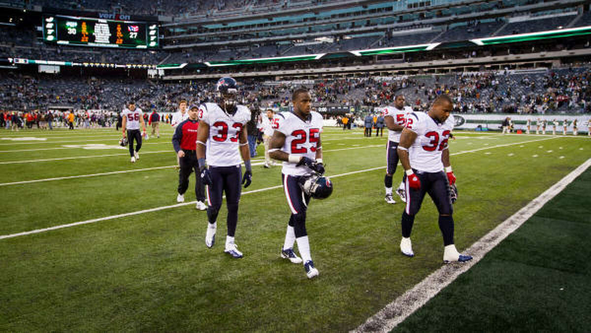 Texans cornerback Kareem Jackson (25), safety Troy Nolan (33) and running back Derrick Ward (32) walk off the field after losing to the Jets.