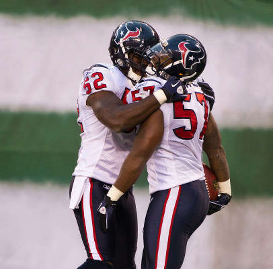 Texans linebackers Kevin Bentley (57) and Xavier Adibi (52) celebrate after Bentley intercepted a pass from Jets quarterback Mark Sanchez late in the fourth quarter. Photo: Smiley N. Pool, Chronicle
